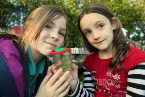 Briar and Mabli from Young Rangers, showing off their latest find during a bug hunt.